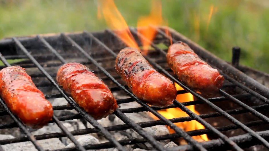 火焰竄起的木炭烤肉爐上頭烤著香腸