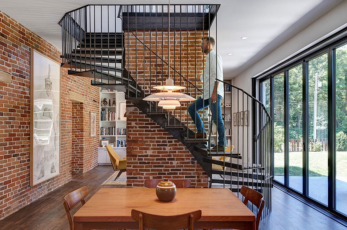 5b6152bbcc430Metallic-spiral-staircase-and-exposed-brick-walls-steal-the-show-on-the-lower-level-living-room