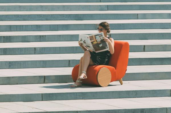 美女坐在戶外紅沙發上看悠閒看報紙