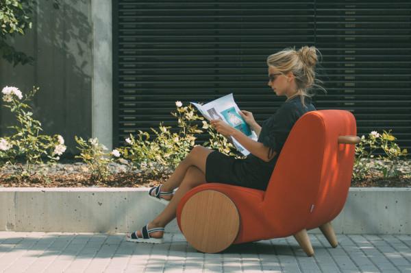 美女坐在紅色布沙發上看雜誌