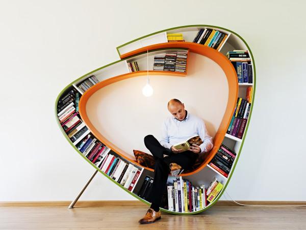 人坐在不規則造型書架上看書