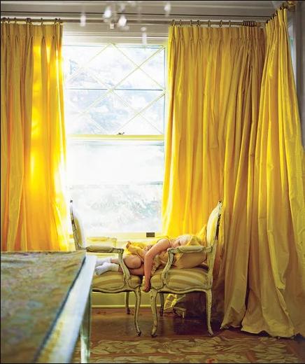 小女孩睡在雙併華麗單人椅上,就在金黃色落地窗簾之前