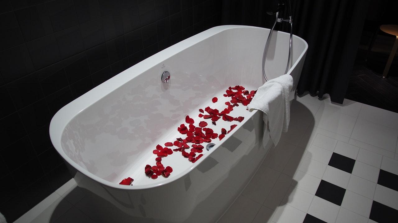 紅色花瓣灑佈在白色獨立浴缸底部