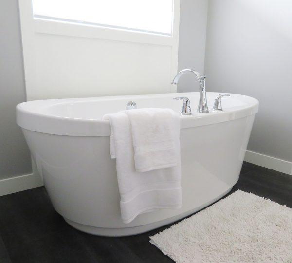 單體浴缸放置在黑色磁磚地板浴室掛著浴巾