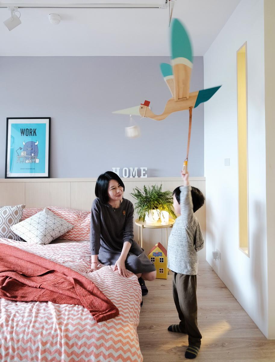 小孩子舉手拿送子鳥玩具