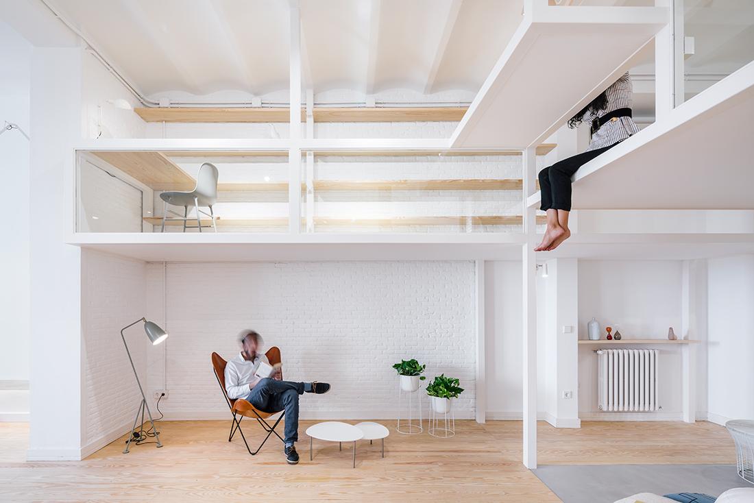 男主人悠閒地坐在屋內白色高架地板下