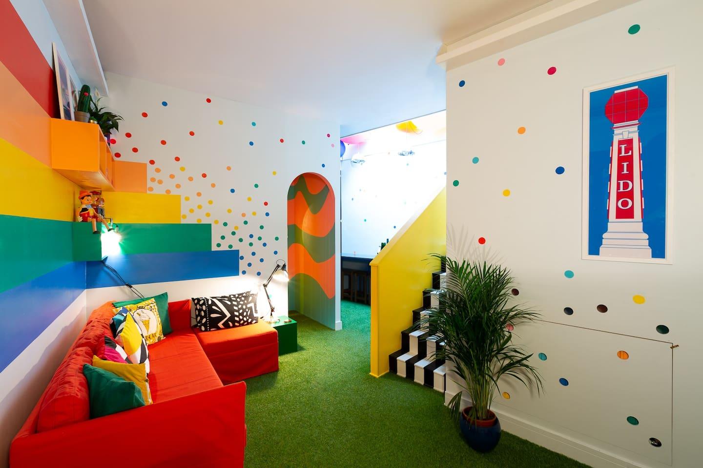 黑色相間的樓梯 綠色地毯 紅色沙發 彩色抱枕