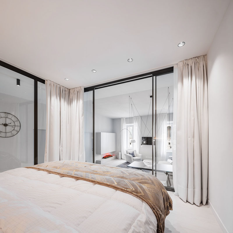 Small Apartment Ideas - This modern small apartment has a raised glass-enclosed bedroom that's able to enjoy the natural light that filters through from the windows in the living room. #SmallApartmentIdeas #SmallApartment #GlassEnclosedBedroom #GlassWalls