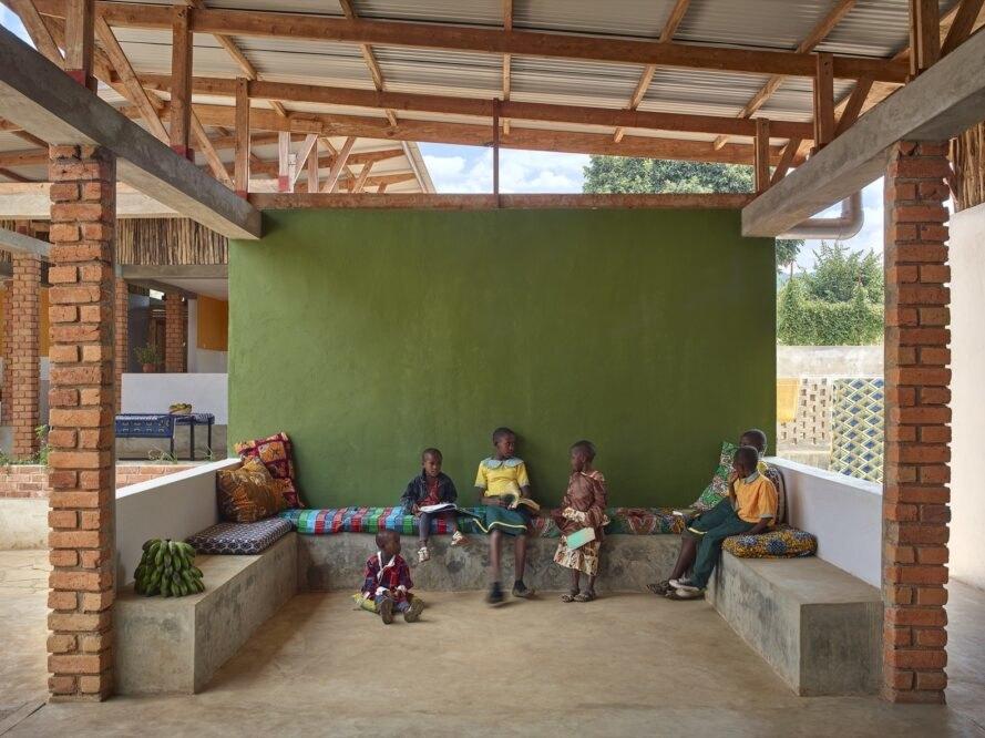 children sit inside a recreation area