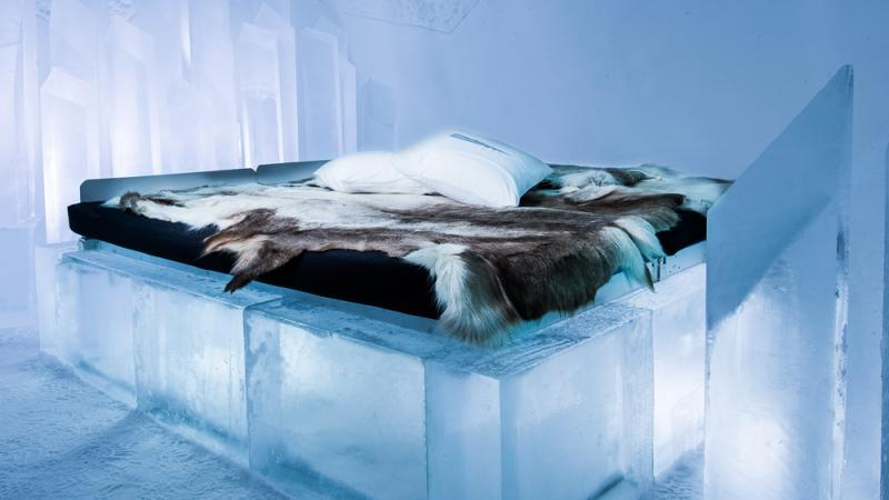 An ice bed with a reindeer fur on it at Icehotel
