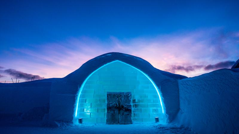 The iconic entrance to Icehotel 29 in blue and purple light