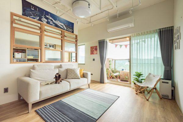 面向落地窗的客廳與白色布沙發、淺木色地板、小灰白雙色地毯