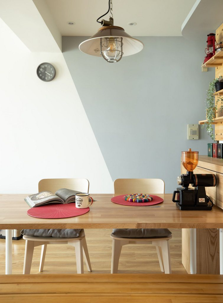 實木餐桌上的磨豆機 敍線灰色牆面